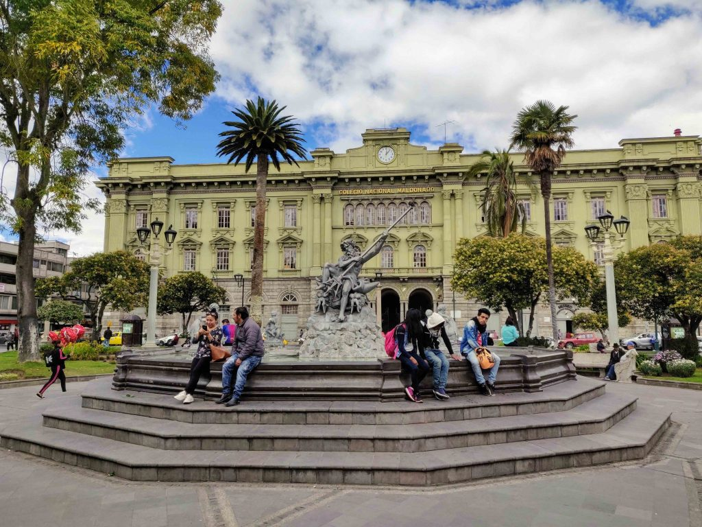 People sitting around Neptune fountain sculpture in Parque de Sucre in front of school