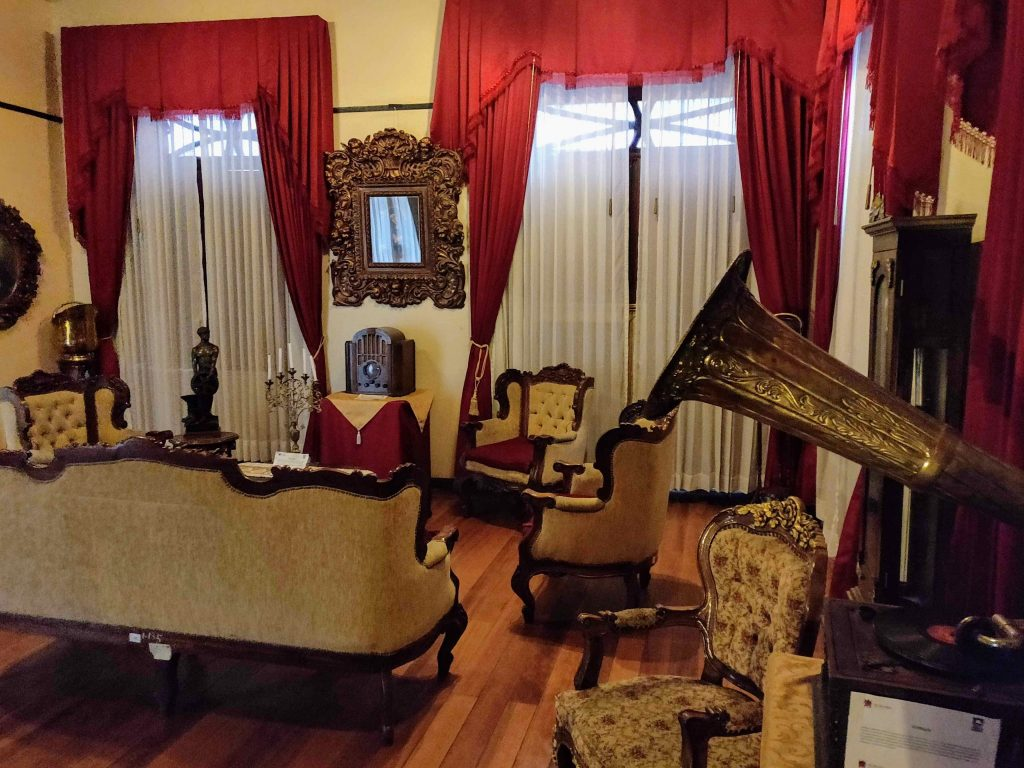 Period furnishings such as couch, record player, chairs, and mirror inside Riobamba City Museum