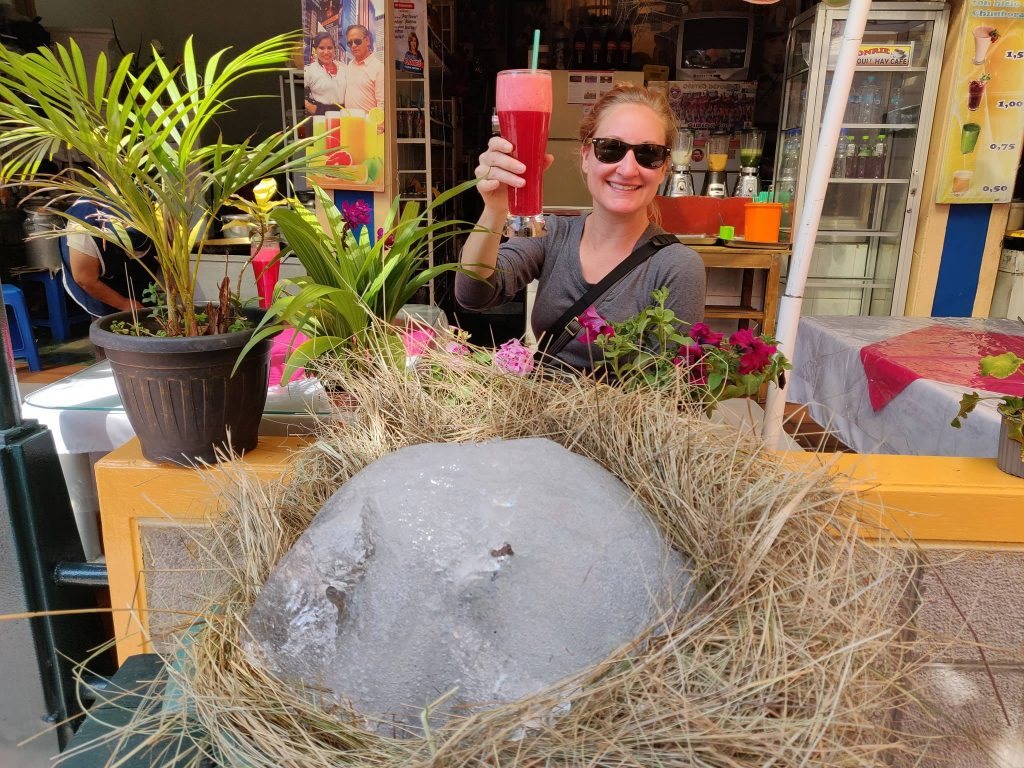 Heather at an outdoor cafe holding up a glass of rompenunca in front of a basket of glacier ice