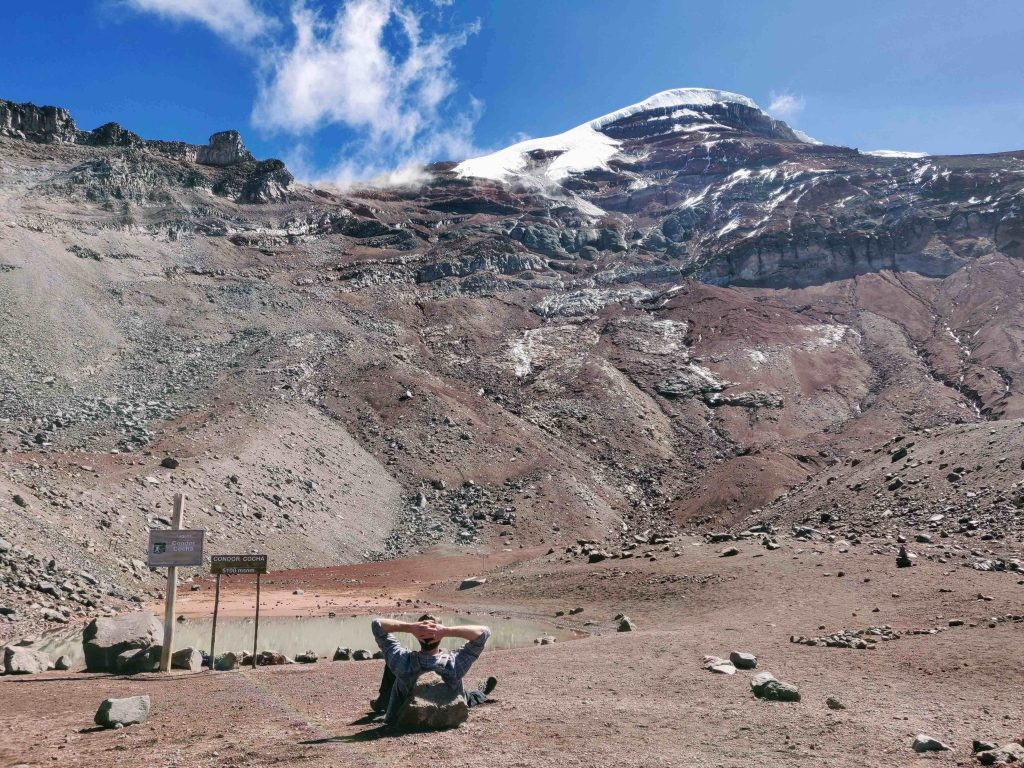 man relaxing in front of small lake on Chimborazo mountain