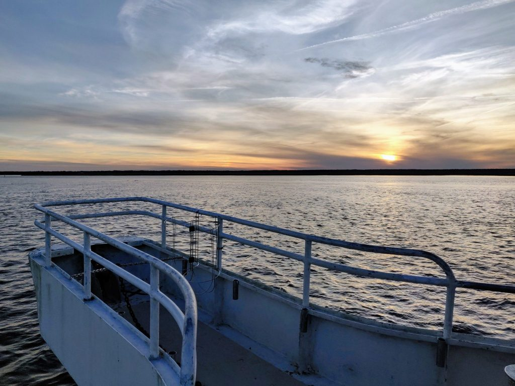 Sunset over the water on the bow of the Cumberland Island Ferry