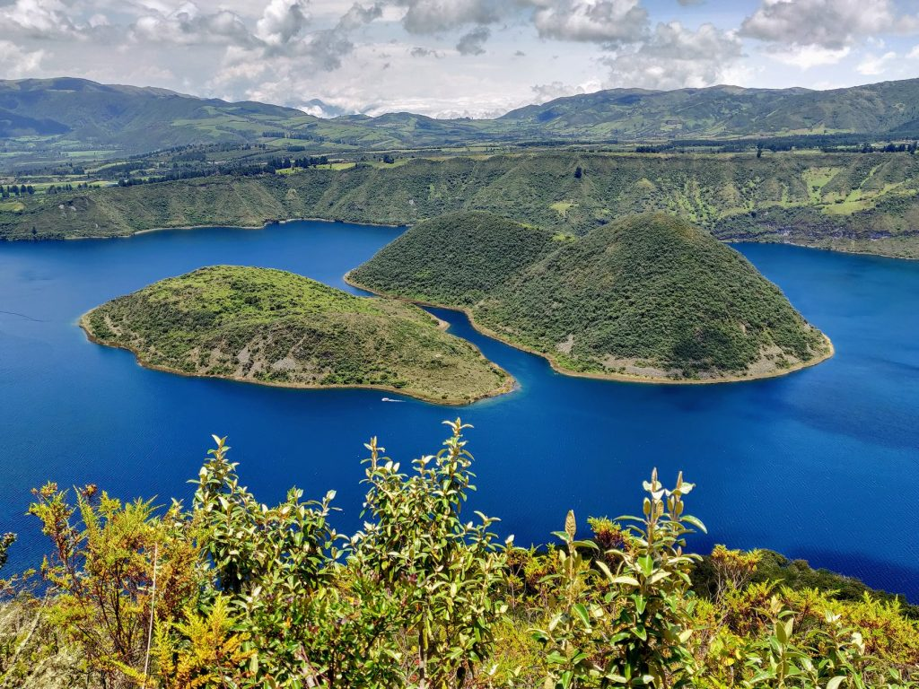 Laguna Cuicocha crater lake with islands that look like guinea pigs in blue lake
