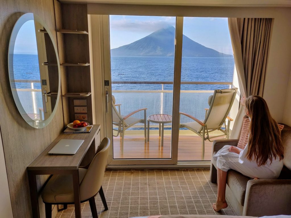 veranda stateroom on a cruise with woman looking out at volcano