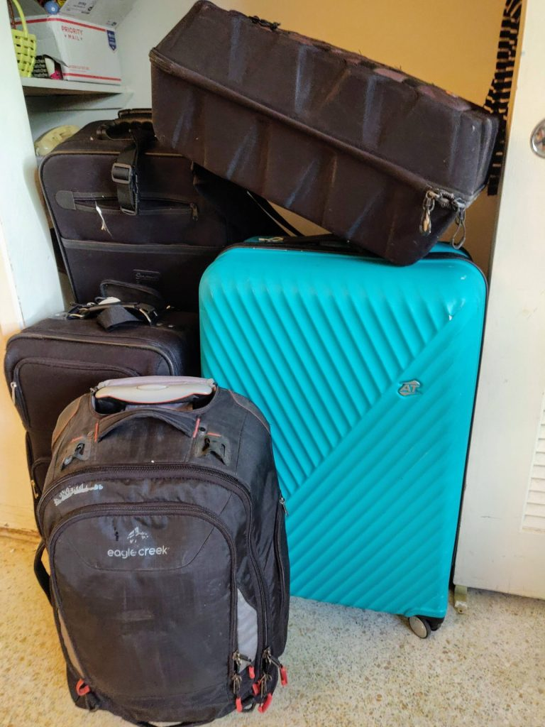 5 pieces of luggage spilling out of a closet